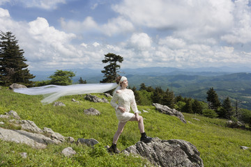 Young bride in black boots on a mountain top