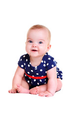 smiling baby girl wearing playsuit sitting on white blanket