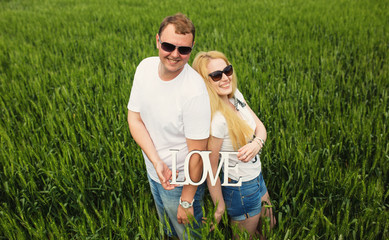 Happy couple standing in wheat field with love word in hands