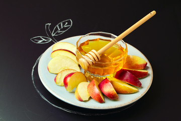 Honey and sliced apple on plate on chalkboard