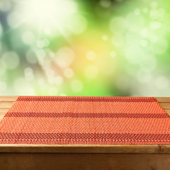 Bamboo tablecloth on wooden table over green bokeh background