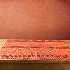Bamboo tablecloth on wooden table over grunge  red background
