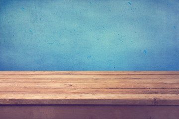 Empty wooden deck table over blue painted wall
