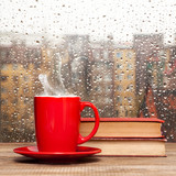 Steaming coffee cup on a rainy day window background