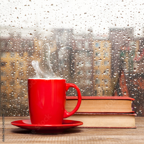 Fotobehang Thee Steaming coffee cup on a rainy day window background
