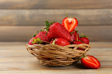Red ripe strawberries in wicker basket on wooden background