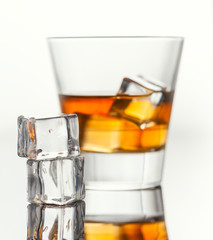 Glass of whiskey with ice, isolated on white background