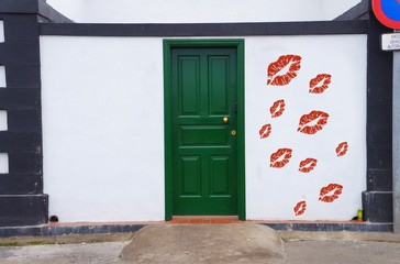 green door with kiss symbol