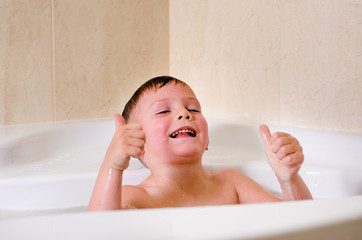 Cute little boy playing in the bath