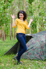 Happy young woman posing in front of a tent