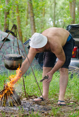 Man lighting a cooking fire while camping