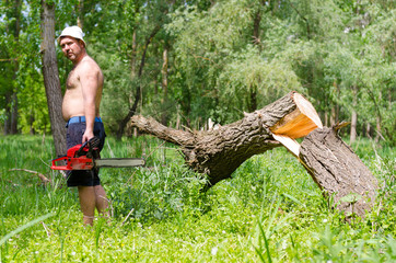 Man standing next to a felled tree with a chainsaw