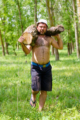 Strong muscular man carrying a large log of wood
