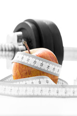 Apple with a tape measure and gym weight