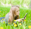 beautiful girl lying on the grass and using tablet computer
