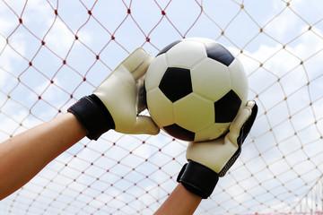 goalkeeper's hands reaching for foot ball