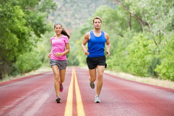 Running young couple outside jogging happy smiling