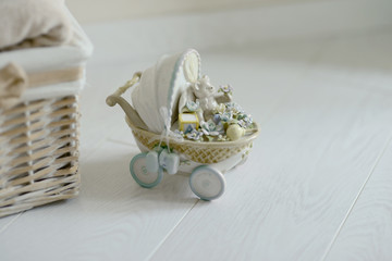 on a white background stands a small buggy with toys handmade