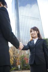 ビルの前で握手をするビジネスウーマンとビジネスマン