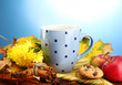 cup of hot tea and autumn leaves, on blue background