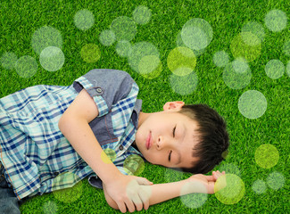 Happy Asian boy sleeping on green grass outdoors