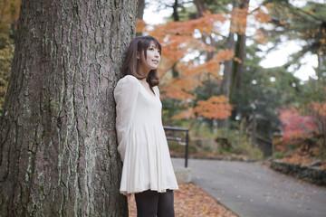 秋の紅葉した公園の大きな木の下で立っている女性
