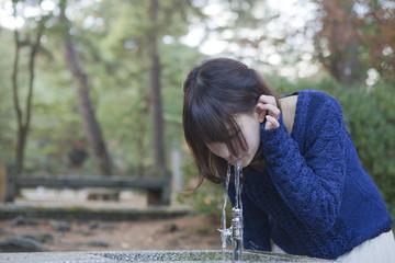 公園の水飲み場の水を飲む女性