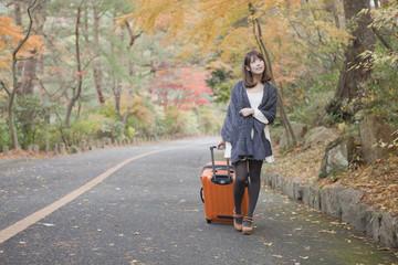 秋の紅葉した公園でトランクを引いている女性