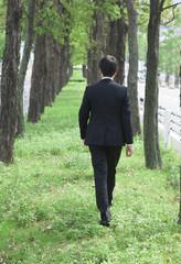 緑の中を歩くビジネスマン