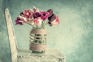 Tulips in a decorated glass jar, photo textured old paper