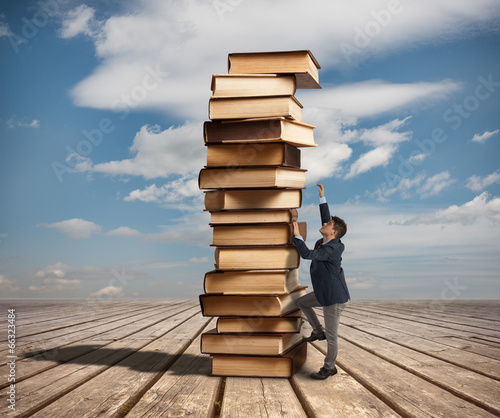 Man climbing a stack of books - 66323484