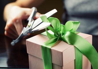 Decorating gift box with green ribbon using scissor