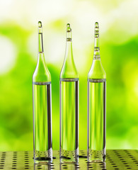Three ampoules on nature background