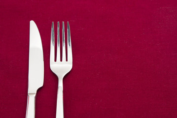 Knife and fork on red tablecloth