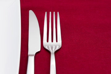 Knife and fork with edge of white plate on red tablecloth
