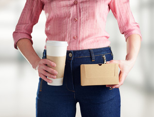 Young woman in deep blue jeans holding a coffee
