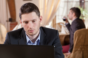 Man working on laptop in restaurant