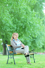 Matrure lady seated on bench in park and holding a book