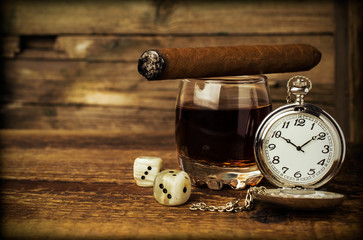 Still life with cognac, cigar , dice and a watch