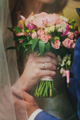 Beautiful wedding bouquet in bride's and groom's hands