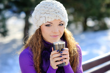 beautiful girl sitting on a bench with a cup of coffee. Winter