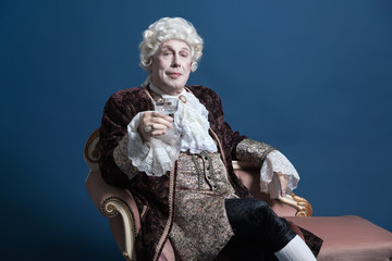 Retro baroque man with white wig holding a wine glass sitting on