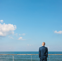 Businessman standing on a roof and looking at the ocean