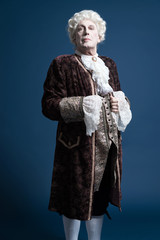 Retro baroque man with white wig standing and looking arrogant.
