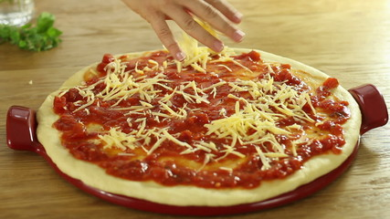 Cook's hand putting cheese on the pizza