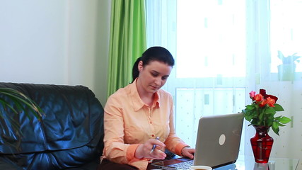 Happy mother working on laptop computer