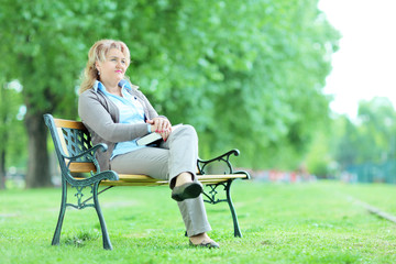 Mature lady relaxing in a park seated on a bench