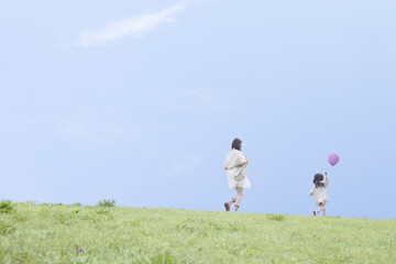 芝生で遊ぶ母と子