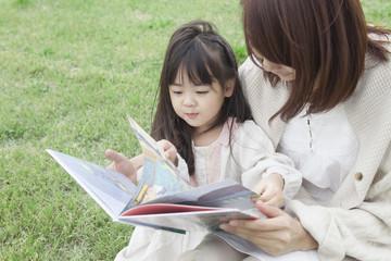 芝生で絵本を読む母と子
