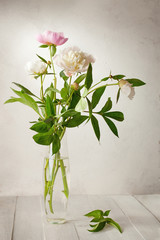 A  bouquet of  pale peonies in a glass vase on wooden table.